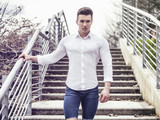 One handsome young man in urban setting in European city, standing, wearing white shirte and jeans - 212824387
