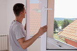 Man Installing New Windows In House - 212824950