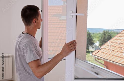 Człowiek instaluje nowe okna w domu