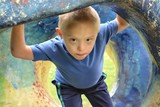 Defect,childcare,medicine and people concept- young boy with a down syndrome who is playing in a park. - 212826106