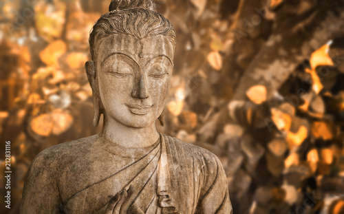 Fotobehang Boeddha holy statue of a buddhist monk praying in front of golden foliage