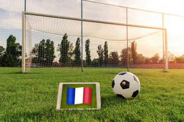 Soccer ball in front of empty goal and flag of France on digital tablet on the grass ;  Bright future