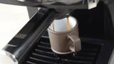Espresso pouring out of a machine into a mug - 212839358