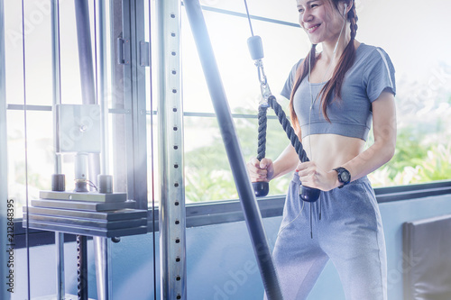 Wall mural Happiness pretty woman exercise with cable weight machine in gym.