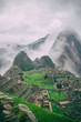 Verical classic view of the ancient mysterious city of Machu Picchu with intense clouds covering the Andes on the background in Peru. Astonishing wallpaper image.