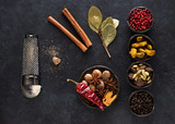 Indian spices and herbs in bowls on a black concrete background, top view, flat lay - 212855560