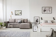 Real photo of a grey couch standing next to a platform bed in spacious one room flat interior - 212857944