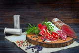Sliced cured sausage and bresaola with spices and a sprig of rosemary. - 212859916