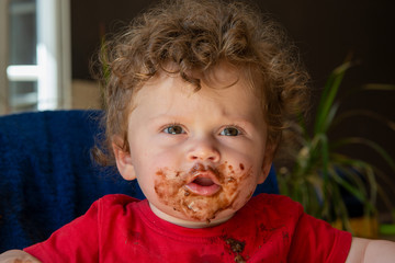 baby is eating a chocolate cake
