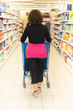 woman goes shopping at the supermarket with her cart in the aisles - 212867341