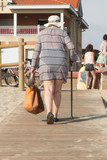 senior woman leaving the beach with her cane and her basket