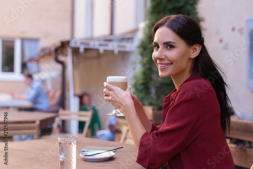 Poster Enjoying coffee. Beautiful elegant woman feeling very rested while enjoying her coffee break in the cafe