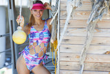 young sexy woman wearing cap and bathing suit summer style, standing on wooden vintage wall with reed in full sunlight - 212869754