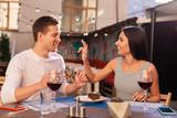 Birthday cake. Smiling beaming woman eating sweet delicious birthday cake sitting near her boyfriend - 212871511