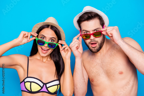 Leinwanddruck Bild Photo of two excited and wondered people with open mouths dressed in swimsuits and hatwear, they are touching colorful glasses, isolated on blue background. Concept of large sales and discount