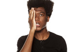 Portrait of young worried african american modern man slapped himself in the face on white background - 212876923
