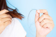 Woman's hand holding hair falling from her head in white t-shirt with blue background. Young Asian female age between 25-35 years old