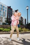 Positive mood. Nice joyful couple having fun while walking in the neighborhood - 212880998