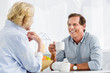 happy elderly couple drinking tea and smiling each other at home