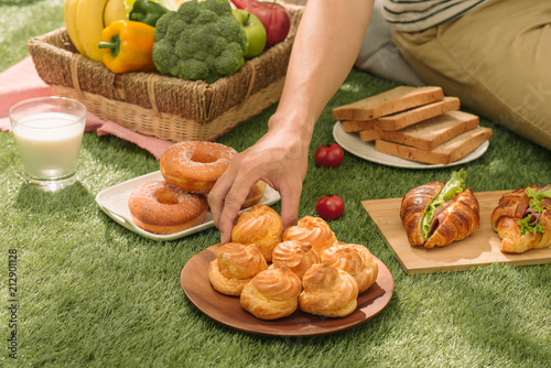 Foto Murales Picnic wicker basket with food, bread, fruit and orange juice on a red and white checked cloth in the field with green nature background. Picnic concept.