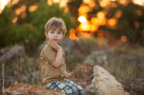 Foto Murales beautiful baby boy on summer sunset background playing