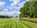 Landscape with green field, trees and a lake in front of the Schwerin castle in Germany in summer. - 212922351