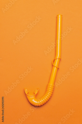 b87309fdc4a Bright orange snorkel tube on yellow background top view