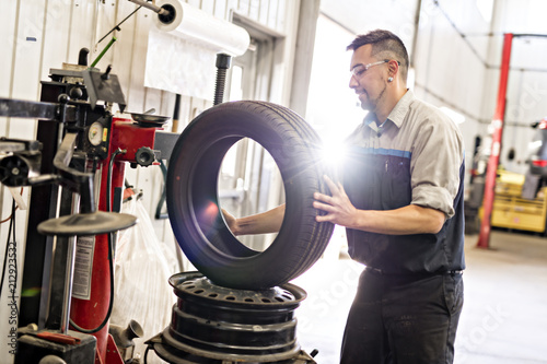 Mechanic changing car tire at work © pololia
