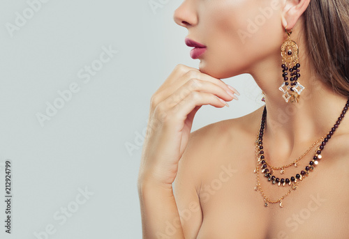 Gold jewelry on woman neck closeup. Necklace and Earrings on female body on background with copy space