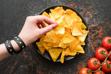 tortilla nacho chips food recipe. woman hand taking a slice of natural fried crisps of a plate - 212927918
