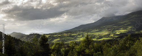 mountain landscape in low evening light with cloudy sky above village and church at the other side of valley - 212929198
