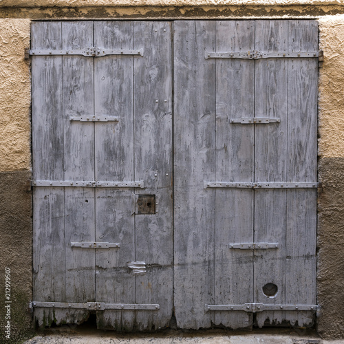 very old weathered blue gray doors in ancient wall of medieval village in french provence