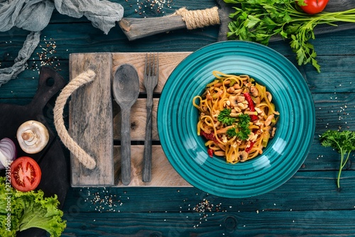 Pasta with mushrooms and vegetables. Italian cuisine. On a wooden background. Top view. Copy space. - 212931991