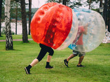People play bumperball zorbsoccer outdoor. summer time