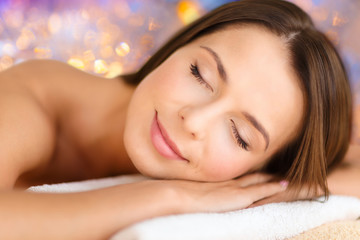 wellness and beauty concept - close up of beautiful woman at spa over holidays lights background © Syda Productions