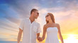 love, summer and relationships concept - happy couple on vacation wearing sunglasses walking and holding hands over sunset sky background