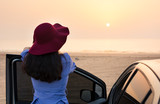 Girl facing beach sunset by the car