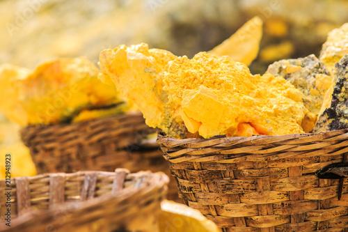 Fotobehang Meloen Baskets full of sulfur ore at Mount Ijen crater lake, Indonesia