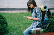 side view of beautiful young woman with backpack using smartphone