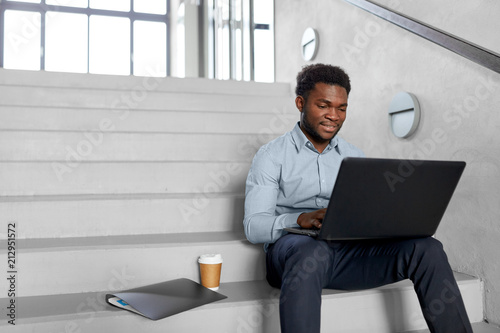 Foto Murales business, people and technology concept - african american businessman with laptop working computer at office stairs
