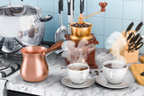 Manual coffee grinder with cups of coffee and copper turkish coffee pot on the kitchen table. 3D rendering - 212954573