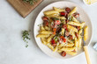 Penne pasta with sausage, bell pepper, cheese and thyme in plate on white wooden background.  - 212956122