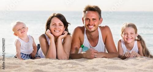 Leinwanddruck Bild couple with two children lying on beach .