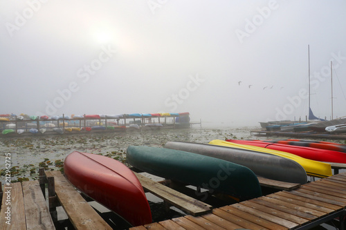 Fotobehang Wit Morning autumn nature misty scene. Scenic view with rising sun penetrate through deep morning fog over the lake, wooden pier and boats on a foreground, rack with kayaks on a background.