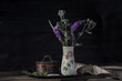 Dark still life with vase and flowers