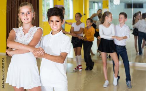 Group of smiling children dancing salsa in school