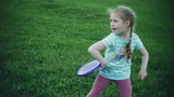 happy woman and daughter playing in frisbee in park - 212970573