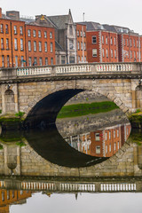 Reflection of buildings and stone bridge in Leffey river