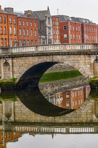 Poster Reflection of buildings and stone bridge in Leffey river