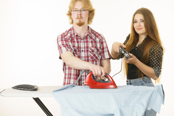 Woman controling man to do ironing